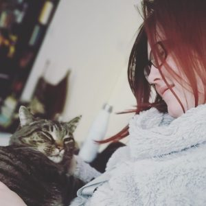 A picture of Kat with Simba the cat sitting on her lap. She is looking down at him lovingly.