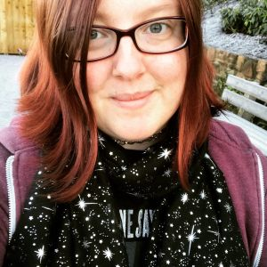 A picture of Kat in her glasses wearing a black scarf with sparkly silver stars. She is smiling at the camera.